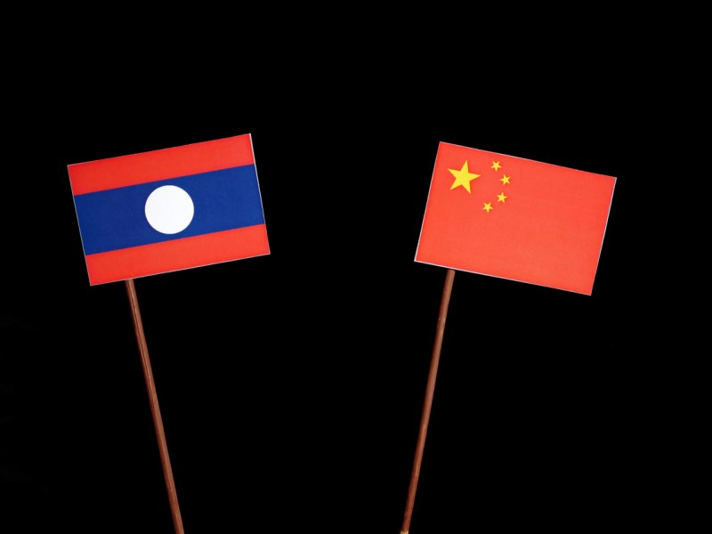 Laos flag with Chinese flag isolated on a black background. Photo: iStock/Getty Images