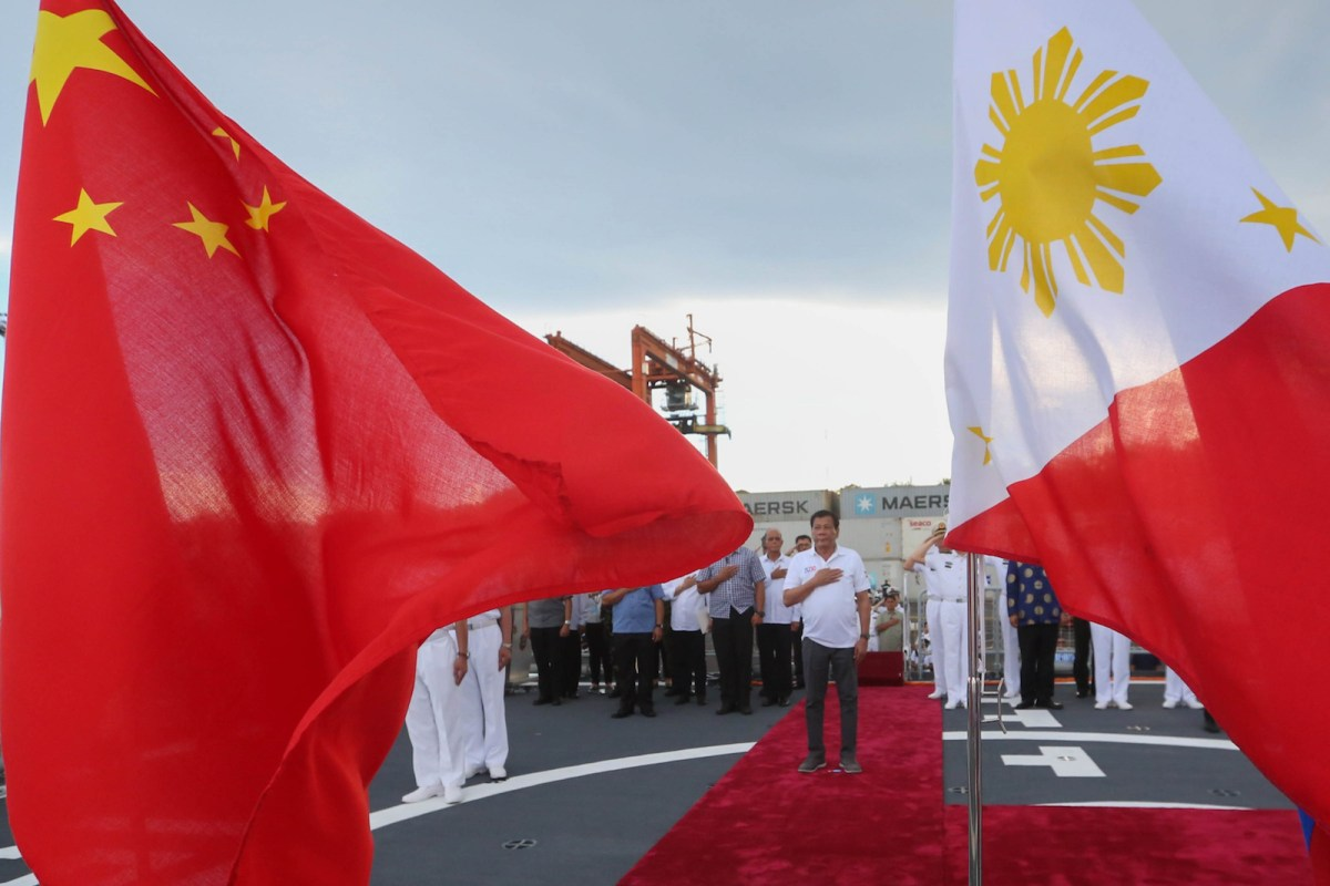 Philippine President Rodrigo Duterte (C) standing in front of Philippine (R) and Chinese national flags during a tour of the Chinese guided missile frigate Changchun berthed at the Davao international port on May 1, 2017. Photo: AFP / PPD/ Simeon Celi