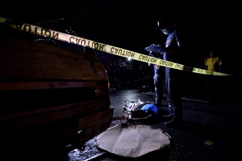 Filipino police officers investigate an alleged drug dealer killed by unidentified gunman in Manila earlier this year.Photo: AFP/ Noel Celis