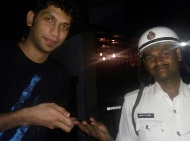 Rajiv collects his friend Pooja's lost iPhone from Constable Ameer Hamza in  Bangalore. Photo: Deccan Chronicle
