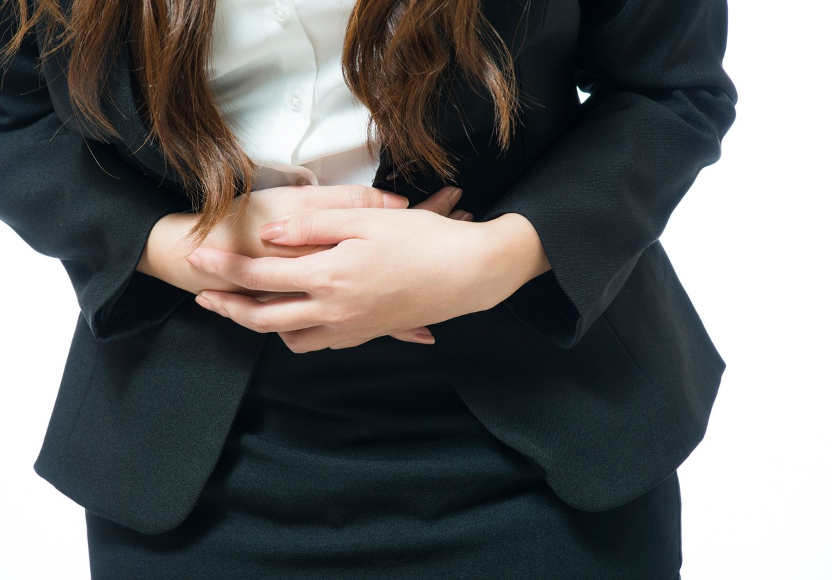 Young businesswoman having back and stomach pain