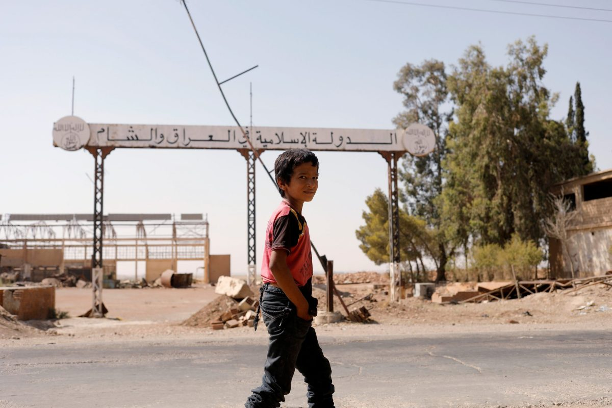 A boy walks past a sign that reads 'Islamic State in Iraq and Syria' in Raqqa, Syria, August 20, 2017. Photo: Reuters / Zohra Bensemra