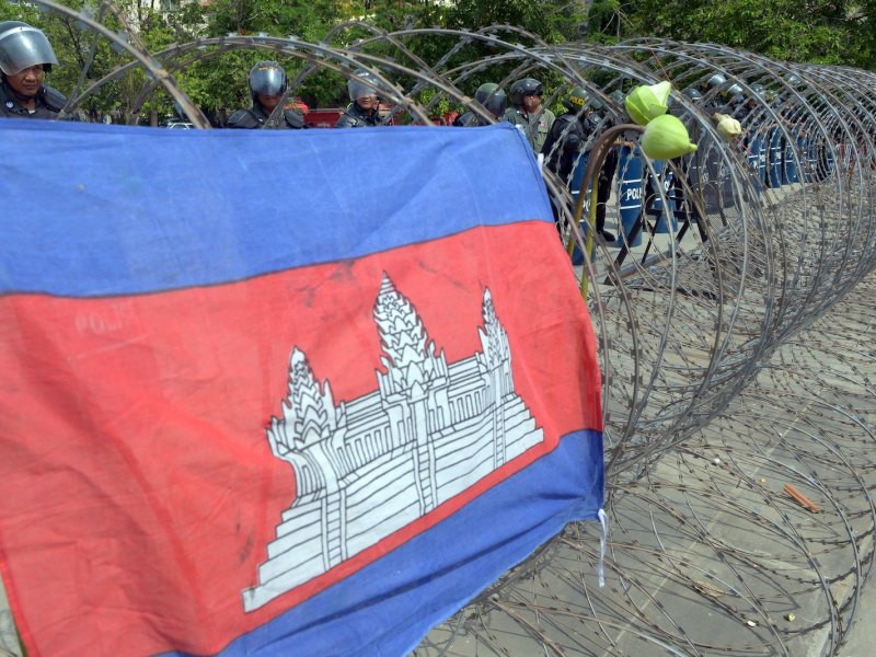 A Cambodian flag is seen on the barbed wire as anti-riot police stand guard during a rally in Phnom Penh on May 1, 2014.  Photo: AFP/Tang Chhin Sothy