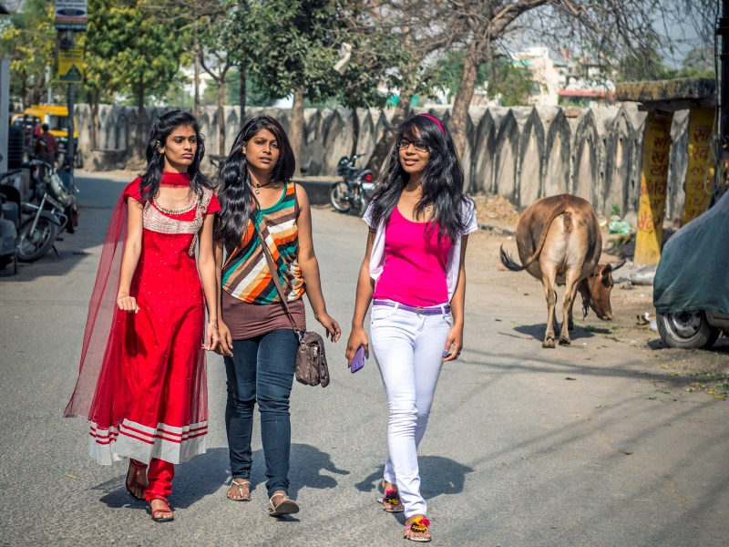 Three young friends walk toward a street market in Udaipur, Rajasthan. Photo: iStock