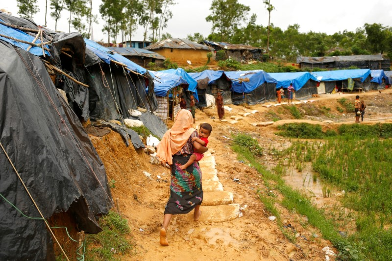 A Rohingya refugee walks on a muddy path as she carries a child at the Kutupalong refugee camp in Cox's Bazar, Bangladesh in this file pic from 2017. Photo: Reuters/ Mohammad Ponir Hossain