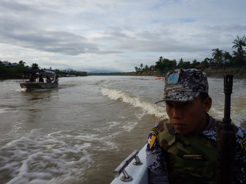 A Myanmar border guard police officer escorts reporters upriver in Buthidaung township, northern Rakhine state, Myanmar July 14, 2017. Photo: Reuters/Simon Lewis