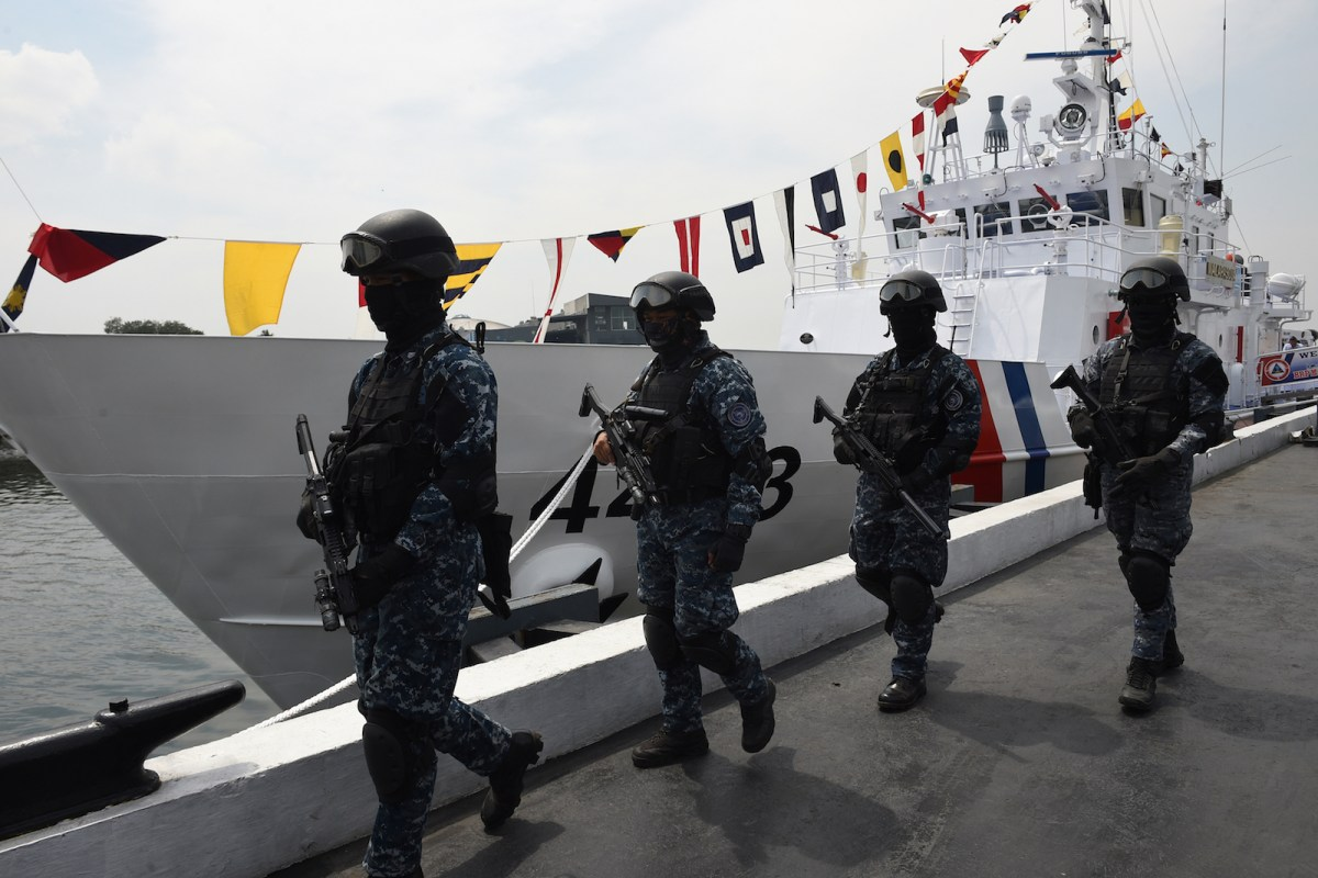 Members of Philippine coast guard anti-terrorism unit stand next to the newly commissioned coast guard's Multi-Role Response Vessel (MRRV) BRP Malapascua during a ceremony at the coast guard headquarters in Manila on March 7, 2017. The multi-role response vessel is one of the 12 coast vessels acquired by the Philippine government from Japan. It will be deployed in Sulu province, where the military has been battling the Abu Sayyaf, a kidnap-for-ransom network that has pledged allegiance to the Islamic State group. / AFP PHOTO / Ted ALJIBE