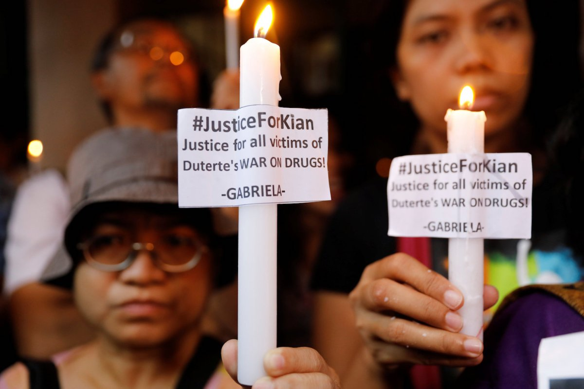 Residents and protesters hold lighted candles at the wake of Kian Loyd delos Santos, a 17-year-old high school student, who was among the people shot dead last week in an escalation of President Rodrigo Duterte's war on drugs in Caloocan city, Metro Manila, Philippines August 21, 2017. REUTERS/Erik De Castro
