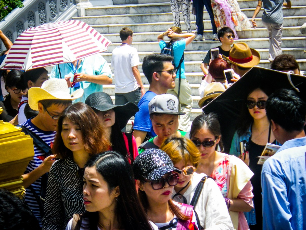 Bangkok, Thailand - June 5, 2016: A large crowd of mainly Chinese tourists are standing at the entrance to the Grand Palace in Bangkok, Thailand.  Several people of mixed age, ethnicity and sex are walking.  Many are using or looking at mobile telephones.  The Chinese tourism market in South East Asia is expanding at a rapid rate.