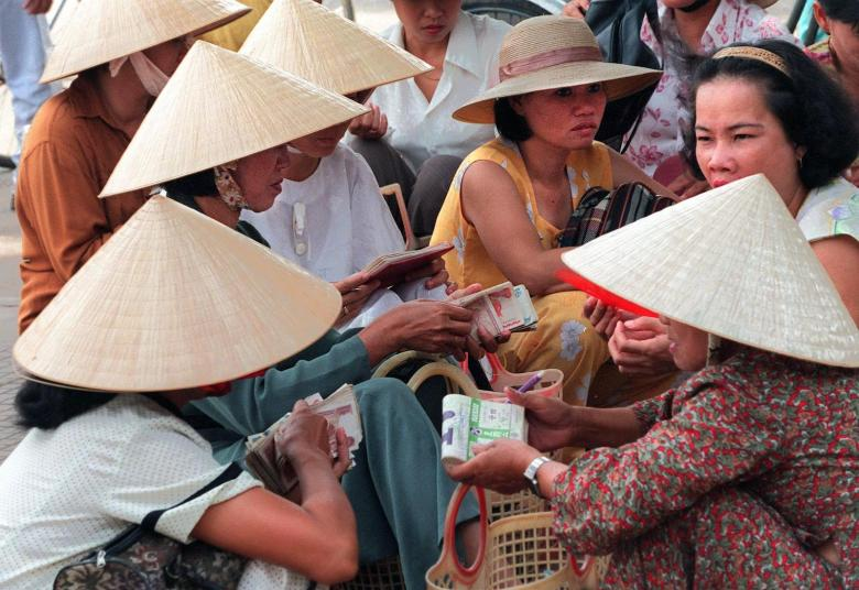 Women count money at Hue's central market in central Vietnam. Non-performing loans topped $241 billion last year. Photo: AFP
