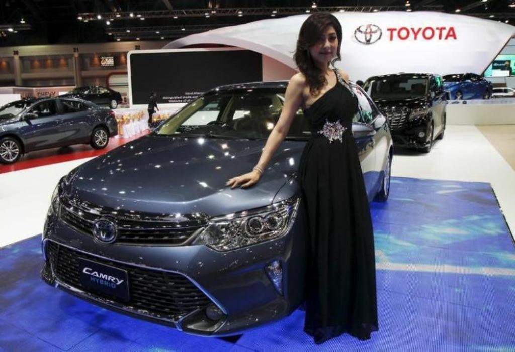 A model poses beside a Toyota Camry Hybrid during the Bangkok International Motor Show in Bangkok. Photo: Reuters