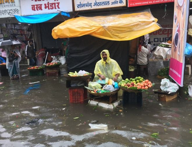 A fruit vendor struggles to cope with flooding in Mumbai. Photo: BBC