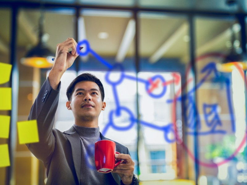 A businessman holds a coffee mug while drawing a graphic on a transparent board. Photo: iStock/Getty