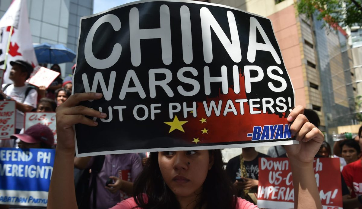 A protester holds a placard during a demonstration in Manila against China's presence in disputed waters in the South China Sea. The Philippines is one of several countries opposed to Chinese expansion in the vital seaway. Photo: AFP / Ted Aljibe