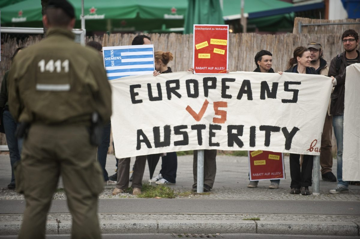 """Greek activists display a banner reading """"Europeans vs austerity"""" as they stage a protest opposite the venue of a meeting of the Federation of German Industry (BDI) in Berlin, on September 27, 2011. Photo: AFP / John MacDougall"""