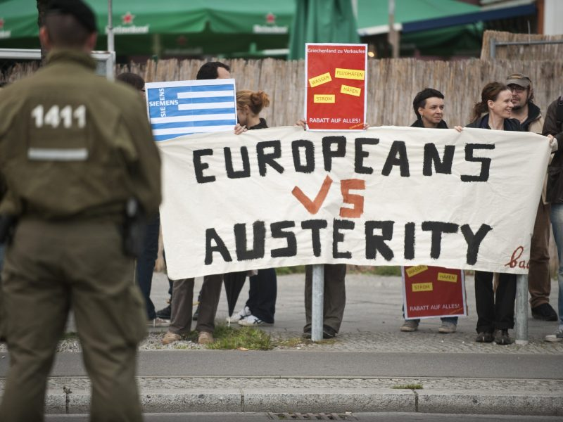 "Greek activists display a banner reading ""Europeans vs austerity"" as they stage a protest opposite the venue of a meeting of the Federation of German Industry (BDI) in Berlin, on September 27, 2011. Photo: AFP / John MacDougall"
