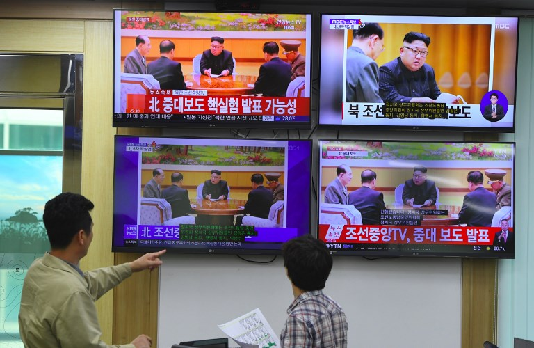 South Korean officials watch television news channels showing North Korean leader Kim Jong-un on September 3, 2017. Photo: AFP