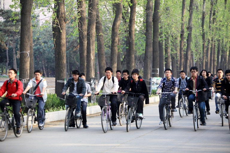 Students ride bicycles on the campus of Tsinghua University in Beijing. The university has been known for training tens of thousands of scientists and engineers for the country since 1949. Photo: AFP