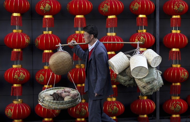 A basket vendor walks past red lanterns outside a shopping mall in Kunming, Yunnan province. Photo: Reuters