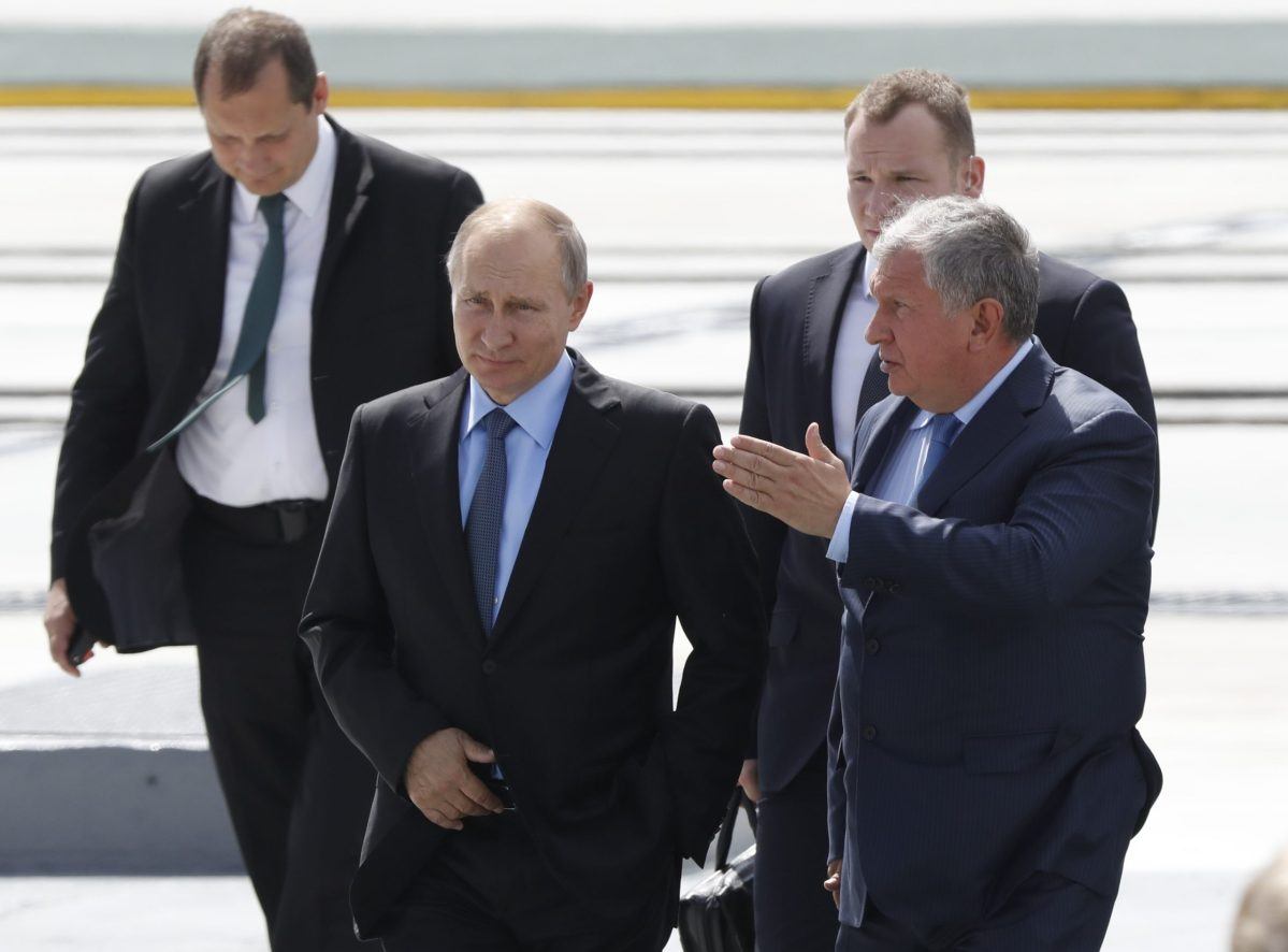Russian President Vladimir Putin (L, front) listens to Rosneft Chief Executive Igor Sechin as he visits the Zvezda shipyard in the far eastern town of Bolshoy Kamen, Russia. Photo: Reuters/Serqei Karpukhin