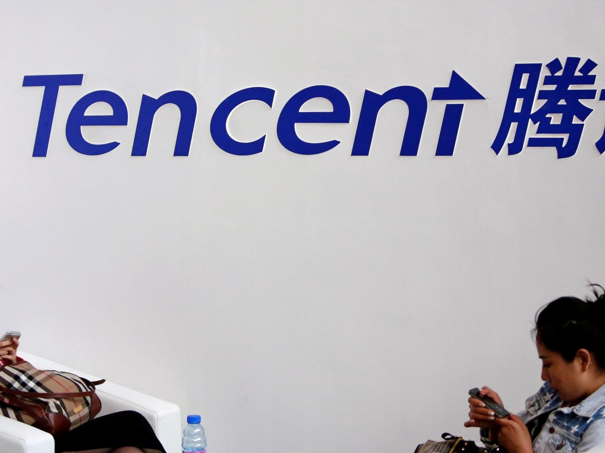 Visitors use their smartphones underneath the logo of Tencent at the Global Mobile Internet Conference in Beijing May 6, 2014. Photo: Reuters/Kim Kyung-Hoon