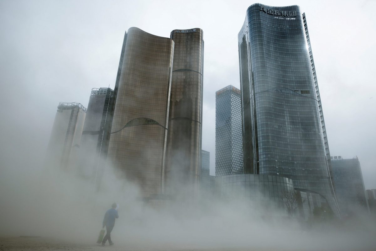 A man walks through dust whipped up by wind at the construction site near newly erected office skyscrapers in Beijing, China April 20, 2017. Reuters / Thomas Peter