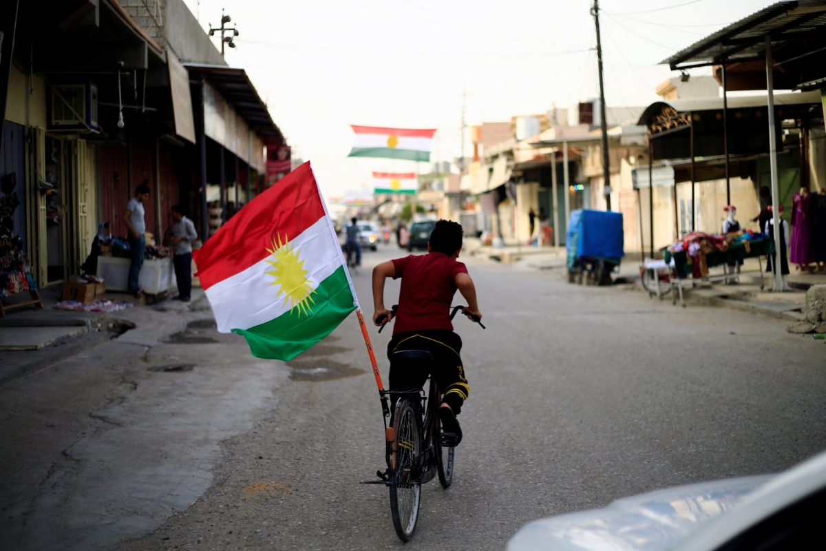 A boy rides a bicycle sporting the flag of Kurdistan in Tuz Khurmato, Iraq, on September 24, 2017. Photo: Reuters / Thaier Al-Sudani