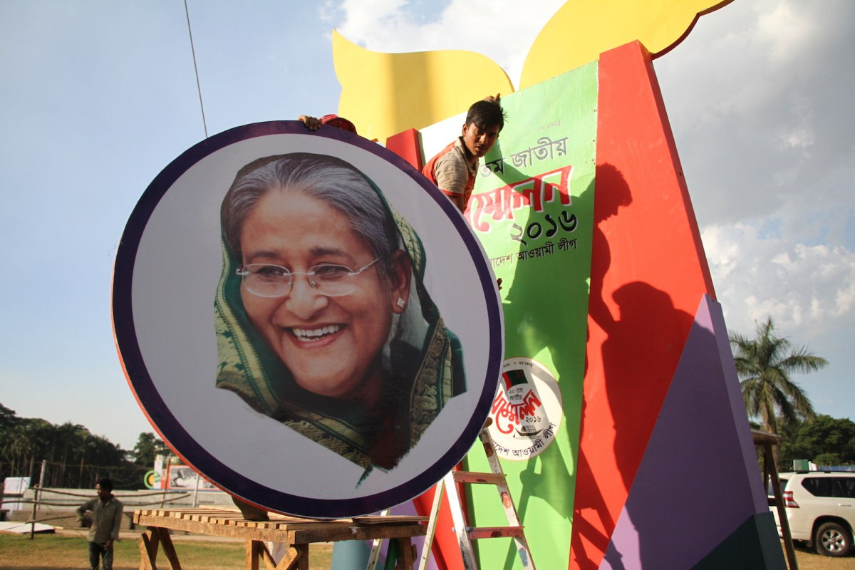 Workers mount a portrait of Bangladeshi Prime Minister Sheikh Hasina ahead of Awami League's National Council in Dhaka, Bangladesh. Photo: NurPhoto via AFP/Rehman Asad