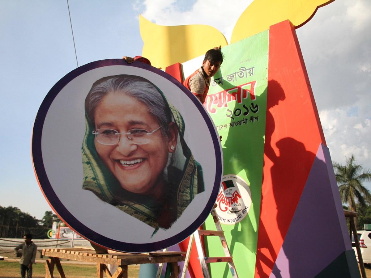 Workers mount a portrait of Bangladeshi Prime Minister Sheikh Hasina ahead of Awami League's National Council in Dhaka, Bangladesh. Photo: NurPhoto via AFP/Rehman Asad