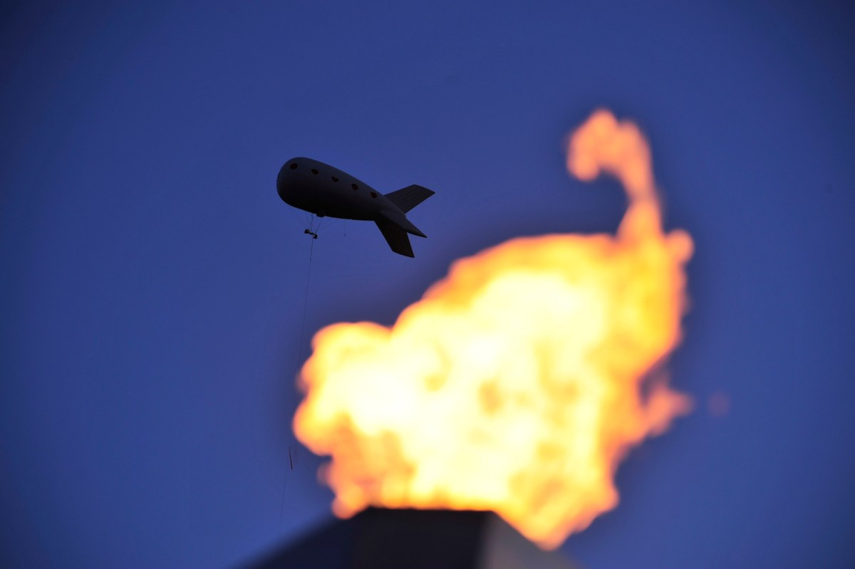 A file photo of a blimp flying over a burning flame. Photo: AFP/Fabric Coffrini