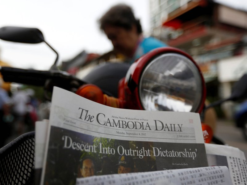 A woman buys a copy of the final issue of The Cambodia Daily at a street stall in Phnom Penh on September 4, 2017. Photo: Reuters / Samrang Pring