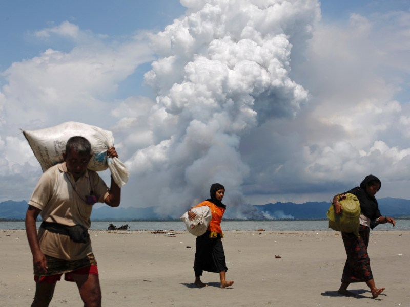 Smoke is seen on Myanmar's side of border as Rohingya refugees walk on the shore after crossing the Bangladesh-Myanmar border by boat through the Bay of Bengal, in Shah Porir Dwip, Bangladesh September 11, 2017. Photo: Reuters/Danish Siddiqui