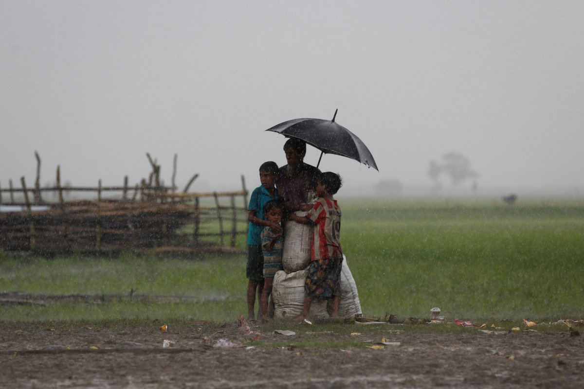 Rohingya refugees stand in an open area with their belongings during heavy rain as they are held by the Border Guard Bangladesh (BGB) after illegally crossing the border, in Teknaf, Bangladesh, August 31, 2017. Photo: Reuters/Mohammad Ponir Hossain