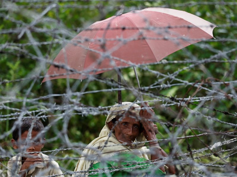 A Rohingya refugee woman and boy looks on through barbed wire as they wait for boat to cross the border through Naf river in Maungdaw, Myanmar, September 7, 2017. Photo: Reuters/Mohammad Ponir Hossain