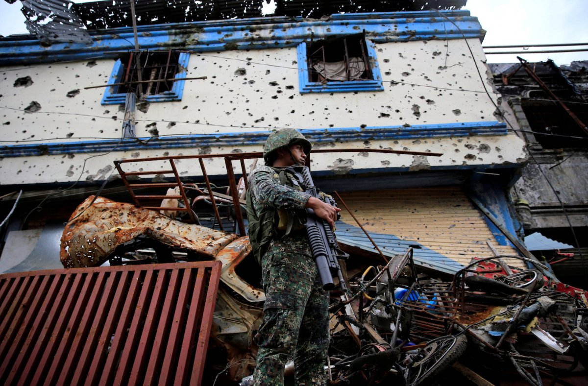 A government soldier stands on guard in front of damaged buildings and houses as troops continue their clearing operations against pro-IS militants who have seized control of large parts of Marawi City, Philippines September 4, 2017. Photo: Reuters/Romeo Ranoco