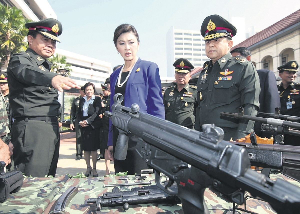 Then Prime Minister Yingluck Shinawatra is given a briefing on various weaponry by then army chief Gen Prayuth Chan-ocha during a visit to the army headquarters in Bangkok, Thailand, 14 December 2011. Photo: Bangkok Post via AFP/Chanat Katanyu