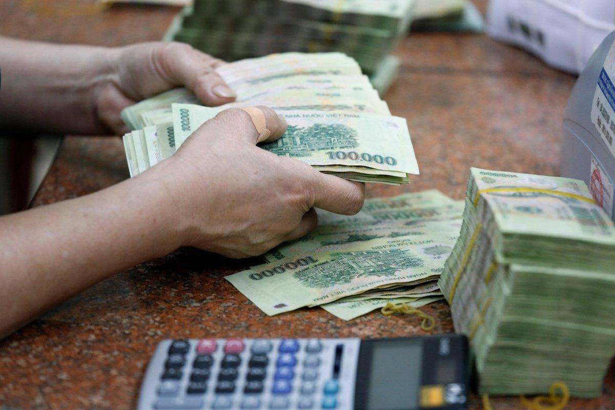 An employee counts Vietnamese banknotes at a branch of Vietinbank in Hanoi, Vietnam September 8, 2017. REUTERS/Kham