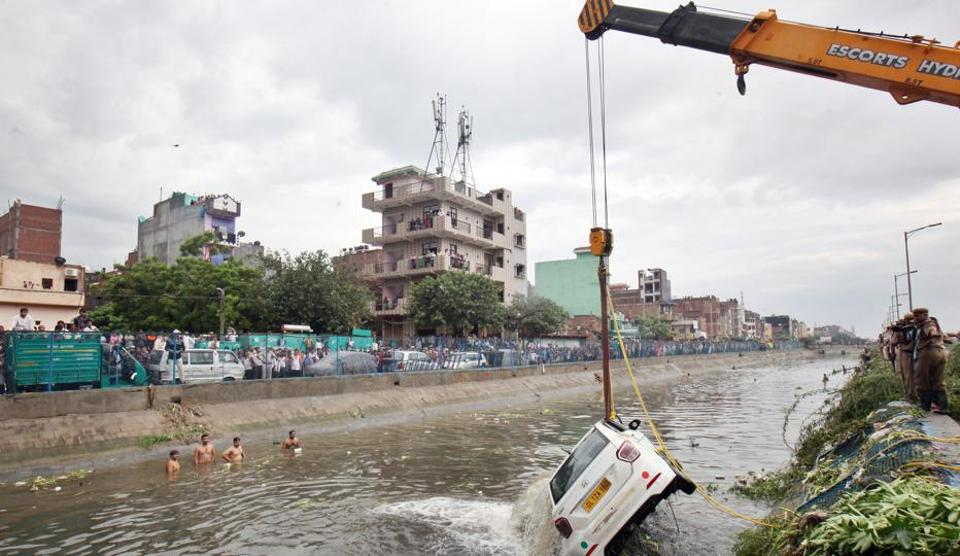 Rescuers remove a car from a canal at the Ghazipur landfill in east Delhi. Photo: Hindustan Times