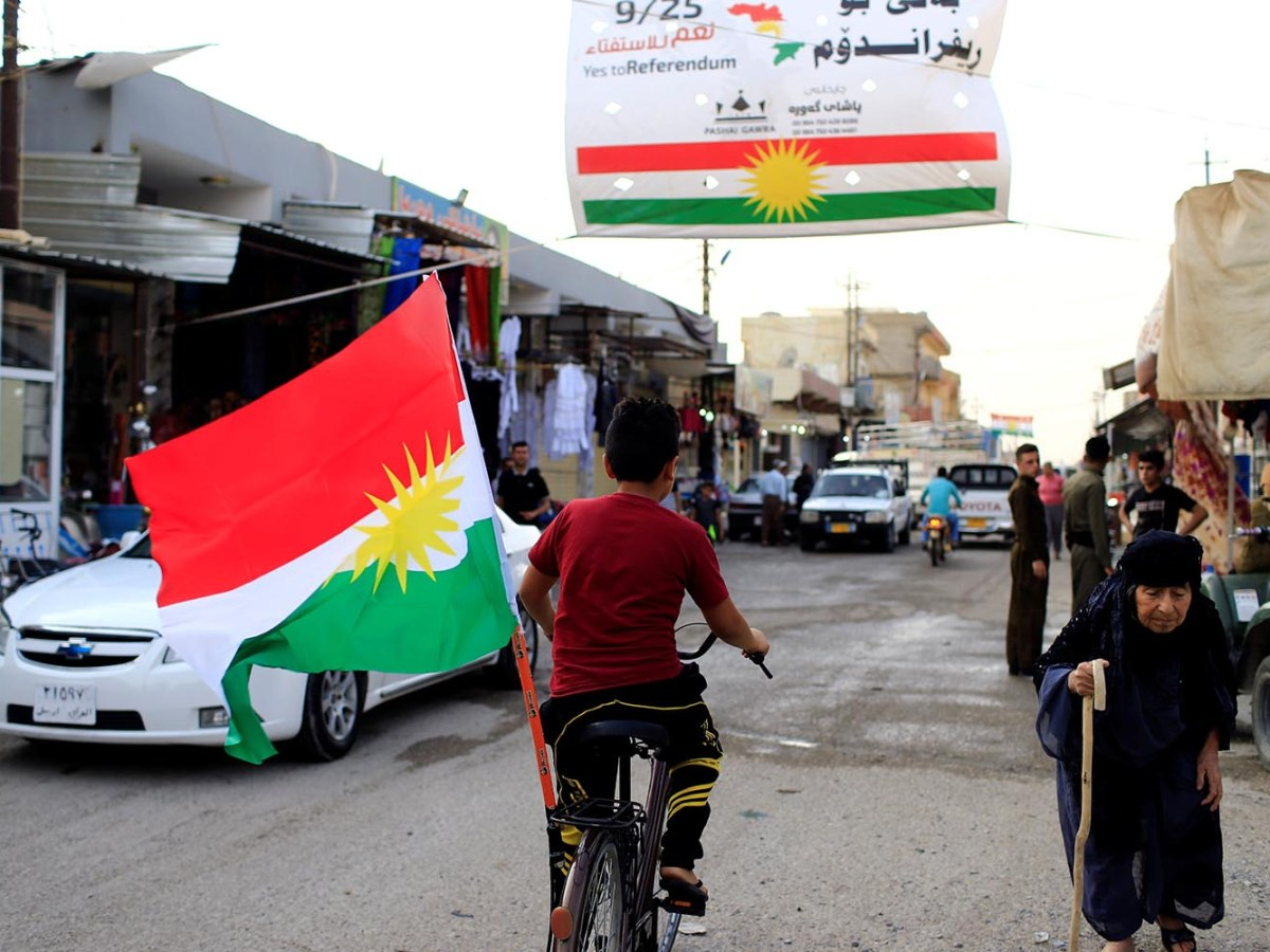 A boy rides a bicycle with the flag of Kurdistan in Tuz Khurmato, Iraq September 24, 2017. REUTERS/Thaier Al-Sudani