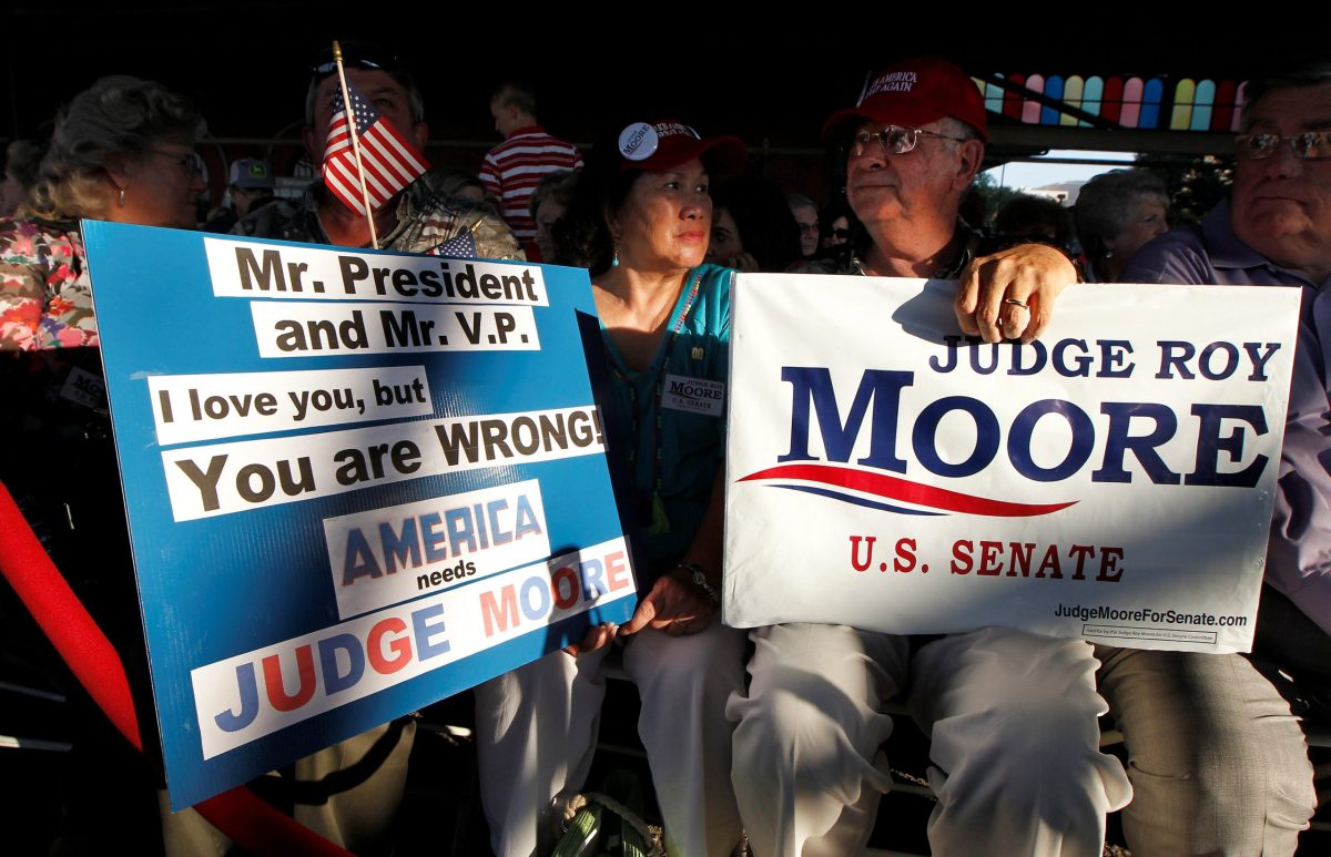 Chu and Joe Green hold signs while waiting for a campaign rally for US Senate candidate Judge Roy Moore at the Historic Union Station Train Shed in Montgomery, Alabama. Photo: Reuters/Tami Chappell