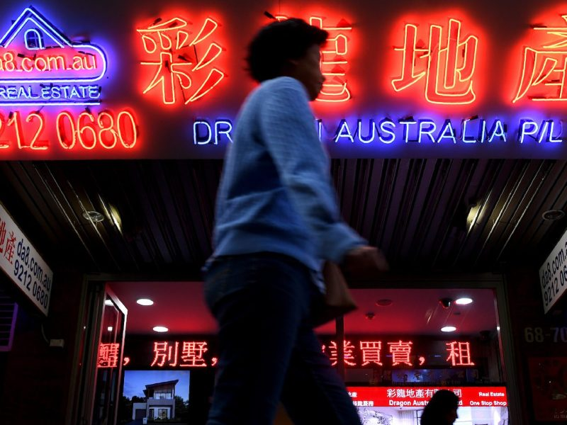 A woman walks by Chinese language advertisements for Australian property in Sydney's Chinatown on June 21, 2017. Photo: AFP/William West