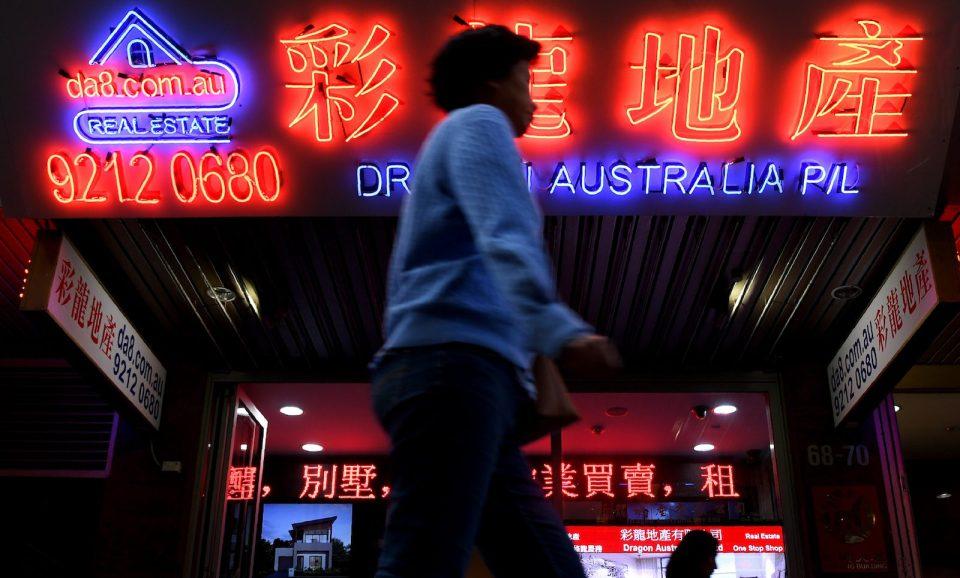 Uma mulher passa por anúncios do idioma chinês para propriedades australianas na Chinatown de Sydney em 21 de junho de 2017. Foto: AFP / William West