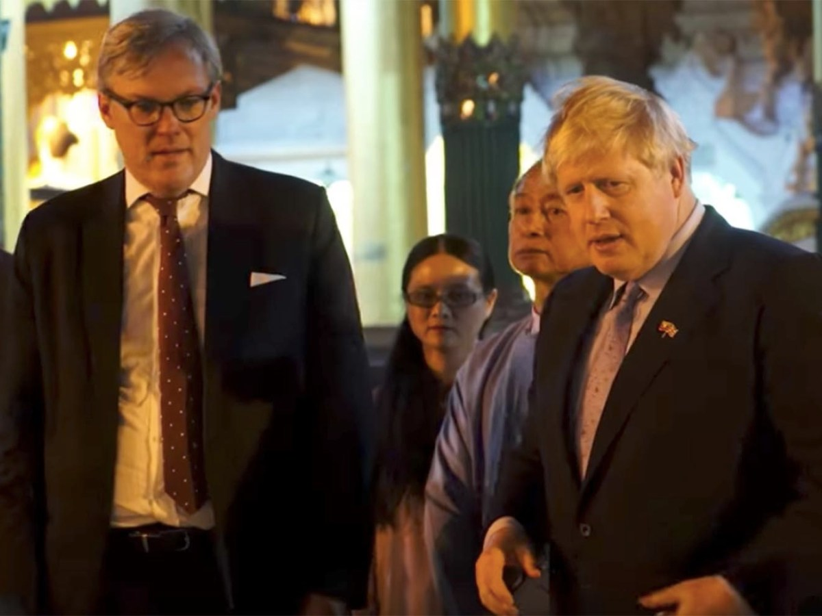 "Boris Johnson (right) recites Rudyard Kipling's racist poem, ""The Road To Mandalay"" while in Myanmar. The UK's Ambassador to Myanmar, Andrew Patrick, pointed out that he was wearing a hot mic and the comment was inappropriate. Photo: Screen grab/ YouTube/Channel 4"