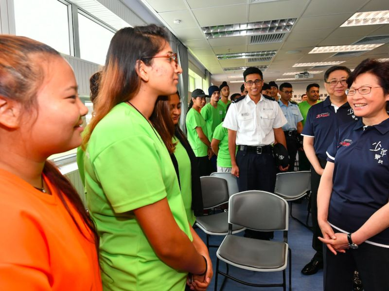 Carrie Lam (right) chats with young members of ethnic minorities in the Junior Police Call Permanent Activity Centre in August. Photo: Hong Kong Government