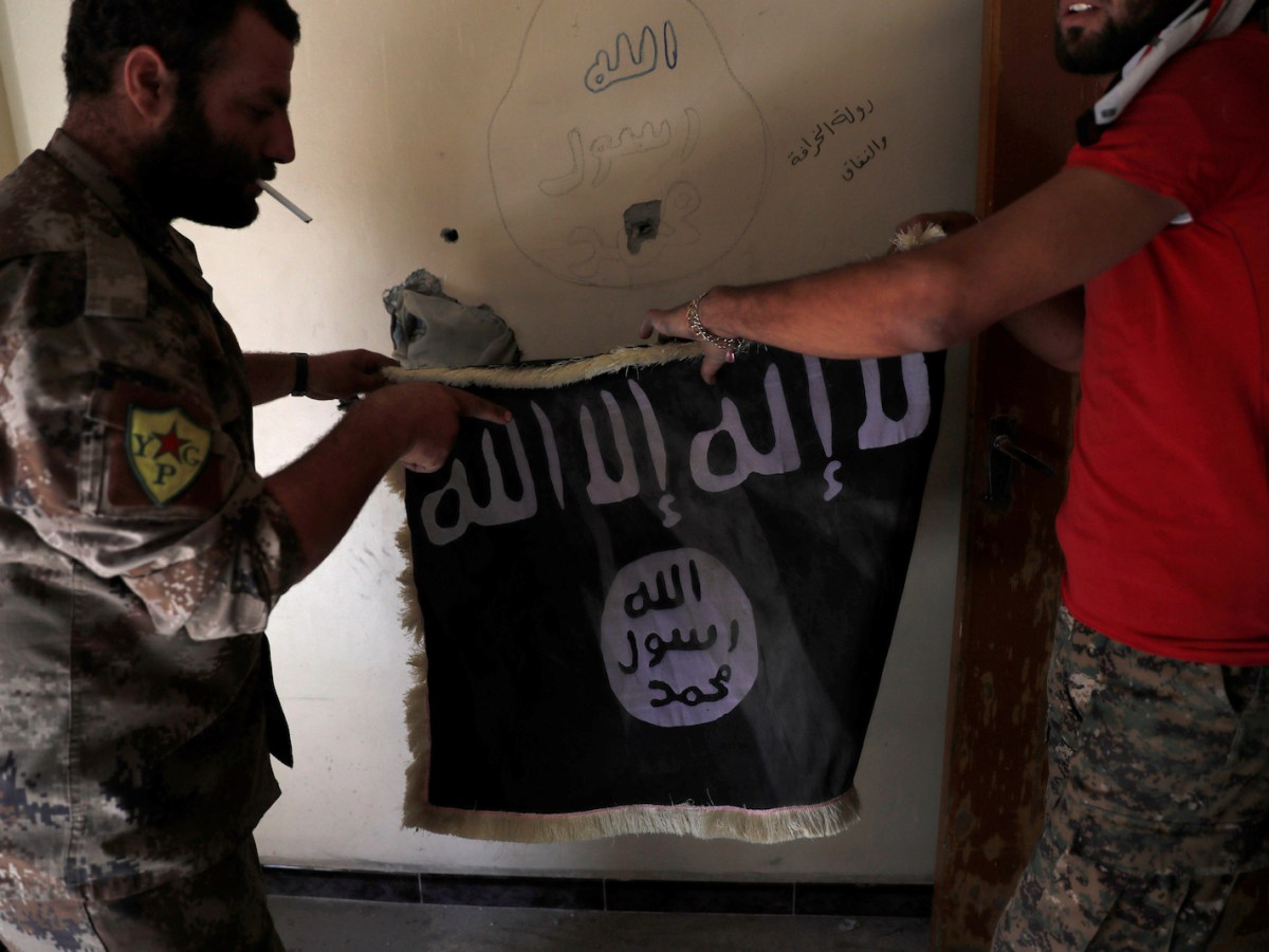 Members of Syrian Democratic Forces hold a flag of the Islamic State militants recovered at a building next to the stadium in Raqqa, Syria, October 4, 2017. REUTERS/Erik De Castro