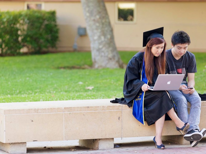 A young woman in a graduation gown sits by a friend at the University of California in this file pic taken in June 2012. Debate has flared about admissions policies at US colleges amid a claim that Harvard discriminates against Asian Americans. Photo: iStock