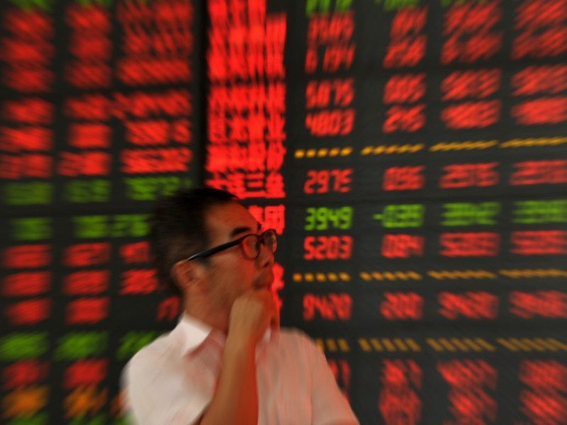 An investor holds watches a board showing stock prices (red for gains). Photo: Reuters