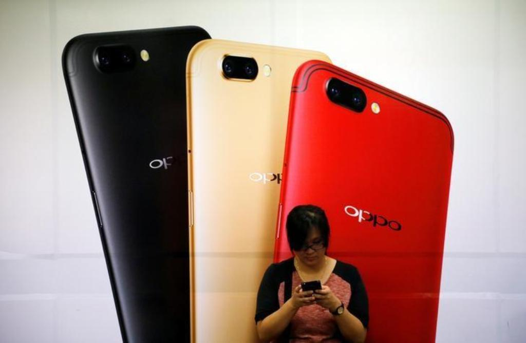 A woman standing Oppo mobile handset advertisement in Singapore _ Reuters