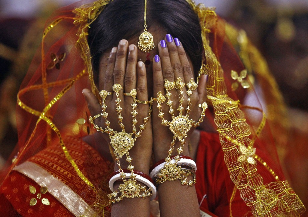 A bride covers her face as she waits to take her wedding vow at a mass marriage ceremony. (Image via Reuters)
