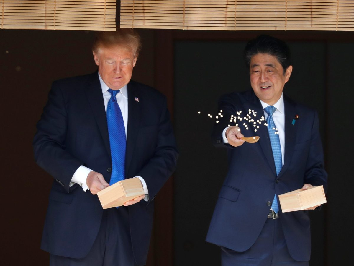 With friends like these... US President Donald Trump and Japanese Prime Minister Shinzo Abe feed fish during Trump's November 2017 visit to Tokyo. Photo: Reuters / Jonathan Ernst